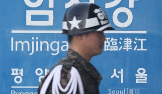 A South Korean army soldier walks by a sign showing the distance to North Korean capital Pyongyang and that for South's capital Seoul from Imjingang Station near the border village of Panmunjom in Paju, South Korea, Thursday, Feb. 14, 2013. (AP Photo/Ahn Young-joon)