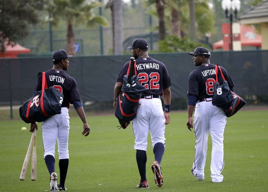 Atlanta Braves outfielders B.J. Upton (2), Jason Heyward (22) and Justin Upton (8) make their way to a practice field during a spring training baseball workout Friday, Feb. 15, 2013, in Kissimmee, Fla. (AP Photo/David J. Phillip)
