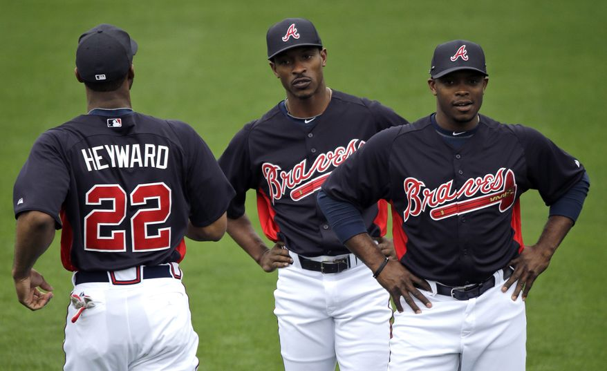 Atlanta Braves outfielders Jason Heyward (22), B.J. Upton, center, and Justin Upton, right, stretch during a spring training baseball workout Friday, Feb. 15, 2013, in Kissimmee, Fla. (AP Photo/David J. Phillip)