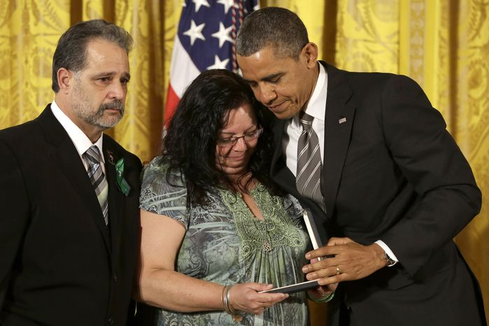 President Obama presents a 2012 Citizens Medal to Donna and Carlos Soto, the parents of slain Sandy Hook Elementary School teacher Victoria Soto, on Feb. 15, 2013, during a ceremony in the East Room of the White House. (Associated Press)