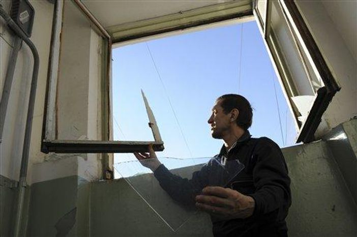 A local resident repairs a window broken by a shock wave from a meteor explosion in Chelyabinsk, about 930 miles east of Moscow, Friday, Feb. 15, 2013. A meteor that scientists estimate weighed 10 tons streaked at supersonic speed over Russia's Ural Mountains on Friday, setting off blasts that injured some 500 people and frightened countless more. (Associated Press)
