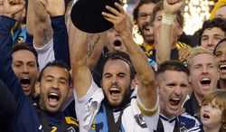 Los Angeles Galaxy's Landon Donovan hoist the trophy as they celebrate after defeating the Houston Dynamo 3-1 in the MLS Cup championship soccer game, Saturday, Dec. 1, 2012, in Carson, Calif. AP Photo/Mark J. Terrill)