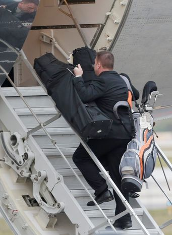 An aide takes several golf bags up the stairs of Air Force One as President Obama prepared to depart from Palm Beach International Airport on Monday in West Palm Beach, Fla. (Associated Press)