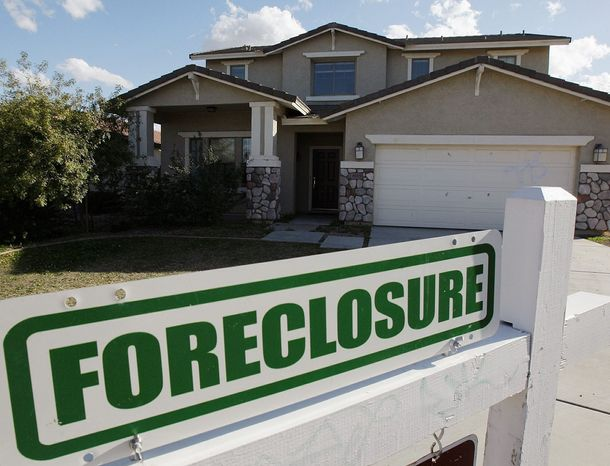 ** FILE ** A foreclosure sign sits outside a home for sale in Phoenix, Tues