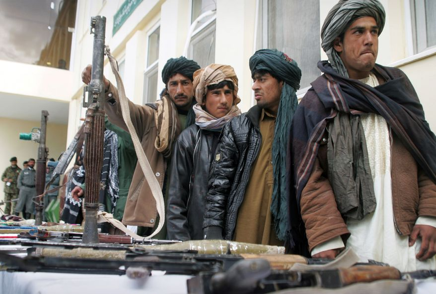 ** FILE ** Former Taliban members who have turned in their weapons stand during a ceremony with the Afghan government in Herat, Afghanistan, on Sunday, Feb. 17, 2013. About 35 former Taliban from Herat province handed over their weapons as part of a peace-reconciliation program. (AP Photo/Hoshang Hoshimi)