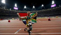 **FILE** Gold medalist South Africa's Oscar Pistorius poses with a flag as he celebrates after winning the men's 400 meters T44 category final during the athletics competition at the 2012 Paralympics, Saturday, Sept. 8, 2012, in London. (AP Photo/Matt Dunham)