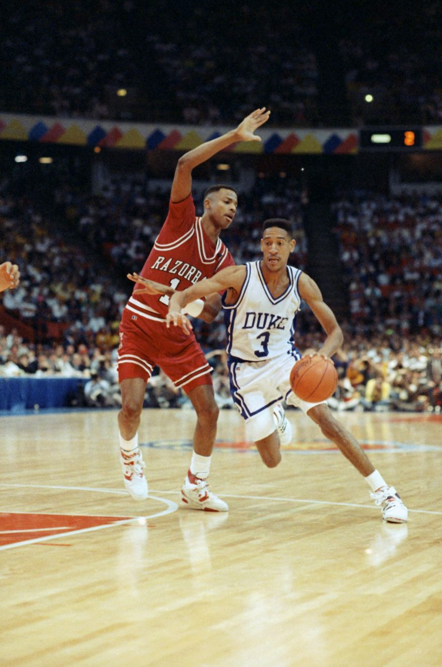 **FILE** Duke University guard Phil Henderson drives around the defense of University of Arkansas forward Todd Day during the second half of semi-final game of the Final Four, March 31, 1990. Both players turned in strong performances. But the Blue Devils topped the Razorbacks 97-83. (AP Photo/Ed Reinke)