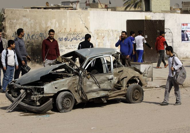 Iraqis inspect a destroyed car at the scene of a car bomb attack in eastern Baghdad on Sunday, Feb. 17, 2013. A series of car bombs exploded within minutes of one another as Iraqis were out shopping in and around the capital, killing and wounding scores of people, police said. (AP Photo/Khalid Mohammed)