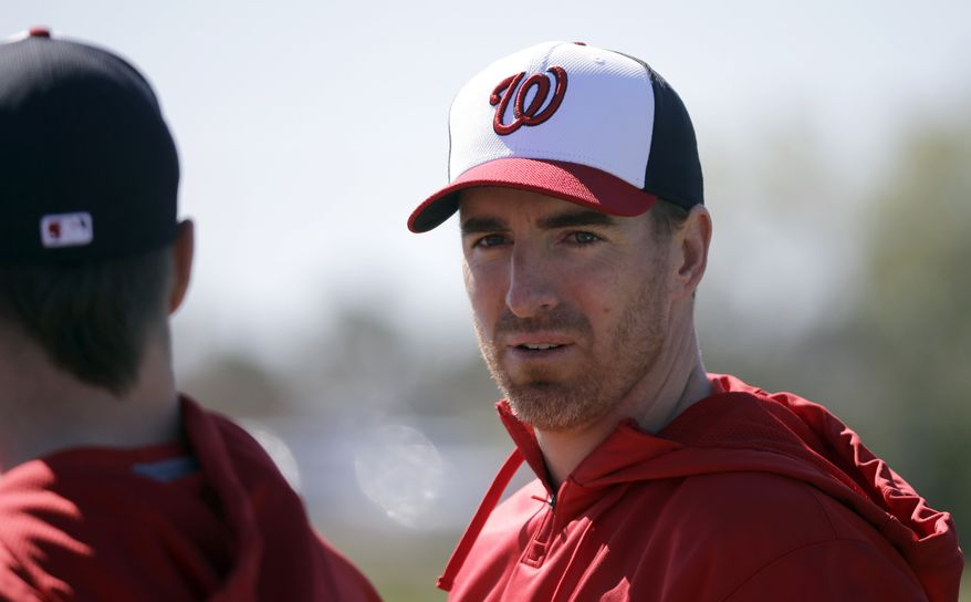 Washington Nationals first baseman Adam LaRoche, right, talks with outfielder Bryce Harper, left, during a spring training baseball workout Sunday, Feb. 17, 2013, in Viera, Fla. (AP Photo/David J. Phillip)