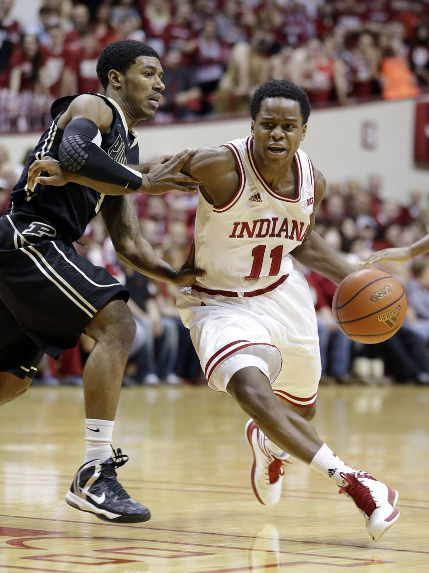 Indiana guard Yogi Ferrell, right, drives on Purdue guard Ronnie Johnson in the second half of a NCAA college basketball game in Bloomington, Ind., Saturday, Feb. 16, 2013. Indiana defeated Purdue 83-55. (AP Photo/Michael Conroy)