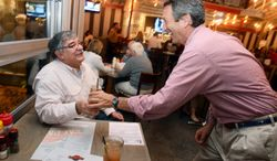 Former South Carolina Gov. Mark Sanford (right), who is running for Congress, serves a drink to Andy Corriveau during the Celebrity Guest Employee Night at Fat Pattie's restaurant in Beaufort, S.C., on Tuesday, Jan. 29, 2013. (AP Photo/The Beaufort Gazette, Jay Karr)
