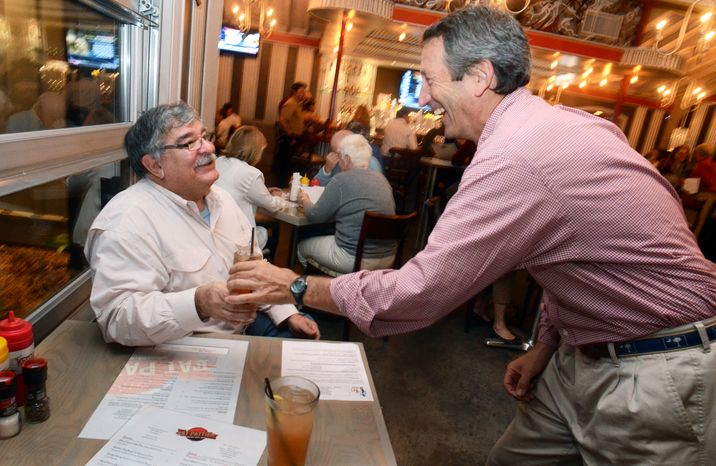 Former South Carolina Gov. Mark Sanford (right), who is running for Congress, serves a drink to Andy Corriveau during the Celebrity Guest Employee Night at Fat Pattie's restauran