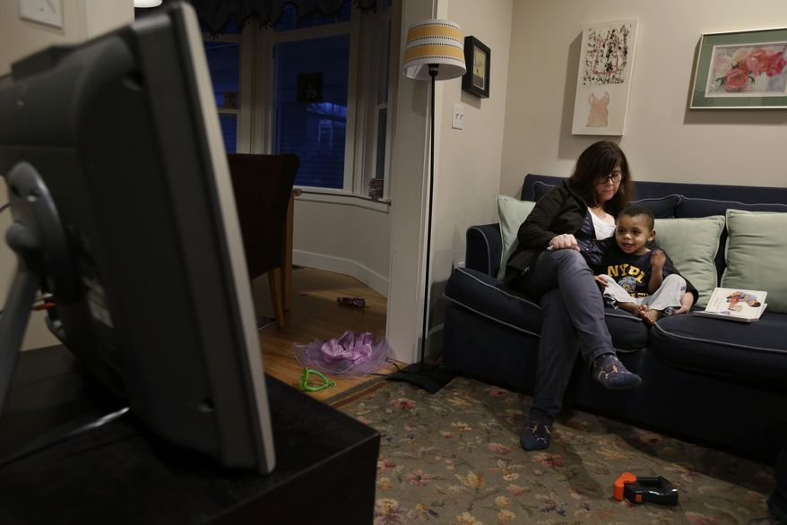Nancy Jensen looks on as her son Joe, 2, gets a special treat of a little TV time on Tuesday, Feb. 12, 2013, at their home in Seattle. Ms. Jensen was a participant in a new University of Washington study on the effects of television viewing on children. (AP Photo/Ted S. Warren)