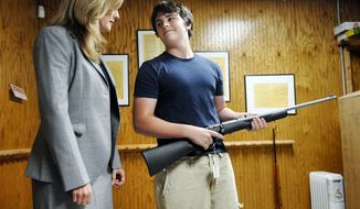 ** FILE ** Michael Steelman (right), 13, smiles at his mother, Missouri state Treasurer Sarah Steelman, after picking out a rifle while shopping at Ammo Alley in Hartsburg, Mo., on May 28, 2008. Mrs. Steelman held a press conference to discuss her support of the Second Amendment to the U.S. Constitution before buying her son the rifle for his birthday. Ammo Alley owner J. Doug Alley helped the two pick out the Marlin 917S 17HMR model. (Nick King Photo/Columbia Daily Tribune/Associated Press)