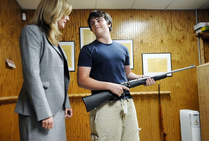 ** FILE ** Michael Steelman (right), 13, smiles at his mother, Missouri state Treasurer Sarah Steelman, after picking out a rifle while shopping at Ammo Alley in Hartsburg, Mo., on May 28, 2008. Mrs. Steelman held a press conference to discuss her support of the Second Amendment to the U.S. Constitution before buying her son the rifle for his birth