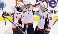 Washington Capitals left wing Alex Ovechkin, center, of Russia, celebrates with defenseman Mike Green (52) and right wing Troy Brouwer (20) after Ovechkin scored the tying goal during the third period of an NHL hockey game against the Florida Panthers, Tuesday, Feb. 12, 2013 in Sunrise, Fla. The Capitals defeated the Panthers 6-5 in overtime. (AP Photo/Wilfredo Lee)