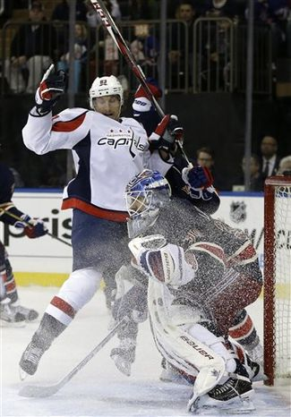 Washington Capitals center Jay Beagle (83) leaps out of the way of a shot on New York Rangers goalie Henrik Lundqvist (30) of Sweden in the first period of their NHL hockey game at Madison Square Garden in New York, Sunday, Feb. 17, 2013. (AP Photo/Kathy Willens)