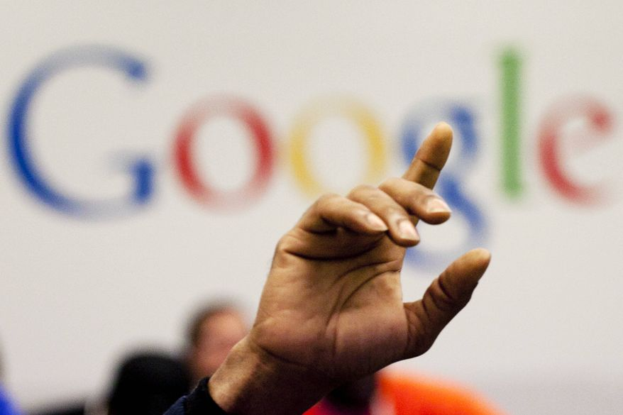 **FILE** A man raises his hand at the Google offices on Oct. 17, 2012. (Associated Press)