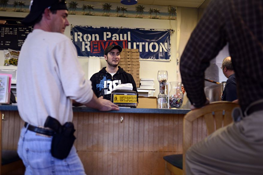 Jay Laze (center) talks with customers including Andy Elliott (left), who brought his 9 mm handgun to All Around Pizza and Deli in Virginia Beach on Monday, Feb. 8, 2013. Any customer at the pizzeria who carries a gun or brings a concealed-handgun permit is offered at 15 percent discount. (AP Photo/The Virginian-Pilot, Amanda Lucier)