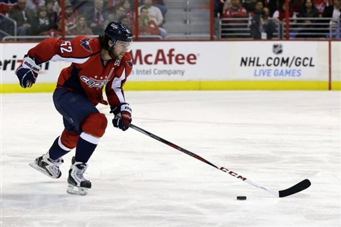 Washington Capitals defenseman Mike Green (52) skates with the puck against the Pittsburgh Penguins during the second period of an NHL hockey game, Sunday, Feb. 3, 2013, in Washington. (AP Photo/Nick Wass)