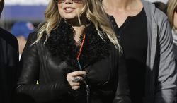 Black Eyed Peas singer Fergie and her husband, actor Josh Duhamel (right), walk on the sidelines during the first quarter of an NFL football game between the San Francisco 49ers and the Miami Dolphins in San Francisco on  Dec. 9, 2012. (AP Photo/Marcio Jose Sanchez)