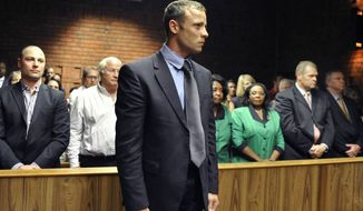 Olympian Oscar Pistorius stands following his bail hearing in Pretoria, South Africa, Tuesday, Feb. 19, 2013. Pistorius fired into the door of a small bathroom where his girlfriend was cowering after a shouting match on Valentine's Day, hitting her three times, a South African prosecutor said Tuesday as he charged the sports icon with premeditated murder. (AP Photo)