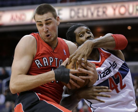 Toronto Raptors center Jonas Valanciunas, left, from Lithuania, and Washington Wizards center Nene (42), from Brazil, vie for a rebound during the first half of an NBA basketball game Tuesday, Feb. 19, 2013 in Washington. A jump ball was called on the play. (AP Photo/Alex Brandon)