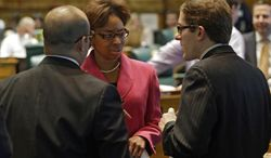 ** FILE ** Rep. Rhonda Fields, D-Aurora, center, talks with Rep. Joseph Salazar, left, and House Speaker Mark Ferrandino, right, D-Denver, about her bill on limiting the size of ammunition magazines at the Capitol in Denver on Friday, Feb. 15, 2013. (AP Photo/Ed Andrieski)