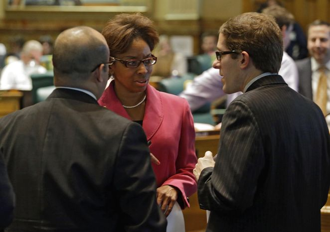 ** FILE ** Rep. Rhonda Fields, D-Aurora, center, talks with Rep. Joseph Salazar, left, and House Speaker Mark Ferrandino, right, D-Denver, about her bill on limiting the size of ammunition magazines at the Capitol in