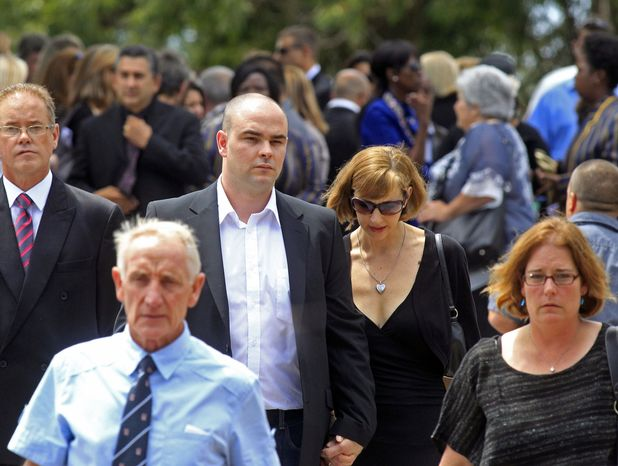 Adam Steenkamp (center left), the brother of Reeva Steenkamp, walks with family members after attending her funeral in Port Elizabeth, South Africa, on Tuesday, F