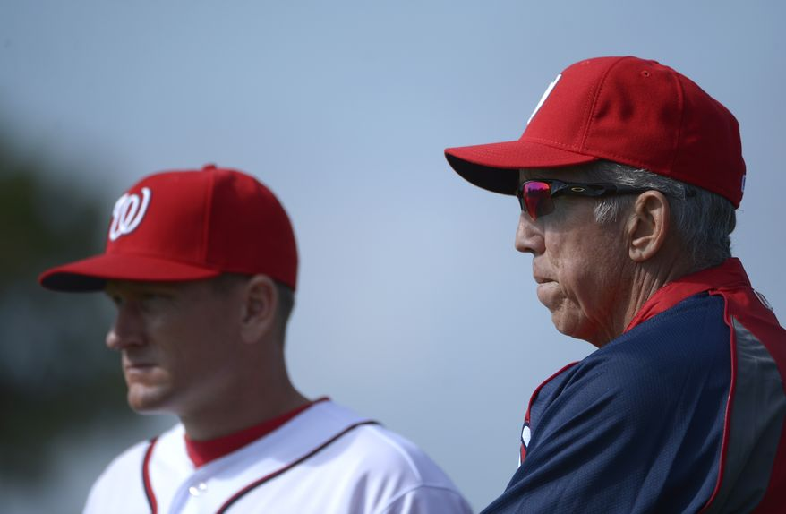 Washington Nationals manager Davey Johnson, right, and batting coach Rick Eckstein watch players warm up during spring training baseball in Viera, Fla., Wednesday, Feb. 20, 2013.(AP Photo/Phelan M. Ebenhack)