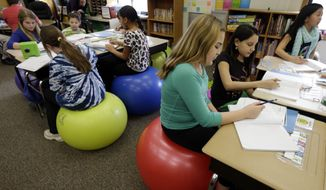 Students in Robbi Giuliano's fifth-grade class sit on yoga balls as they complete their assignments at Westtown-Thornbury Elementary School Monday, Feb. 4, 2013, in West Chester, Pa. By making the sitter work to stay balanced, the balls force muscle engagement and increased blood flow, leading to more alertness. (AP Photo/Matt Rourke)