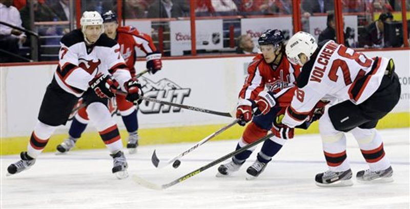 New Jersey Devils defenseman Henrik Tallinder (7), of Sweden, and defenseman Anton Volchenkov (28), of Russia, pressure Washington Capitals center Jay Beagle (83) in the second period of an NHL hockey game, Thursday,