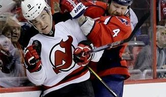 New Jersey Devils right wing Bobby Butler (9) and Washington Capitals defenseman John Erskine (4) collide on the boards in the first period of an NHL hockey game, Thursday, Feb. 21, 2013, in Washington. (AP Photo/Alex Brandon)