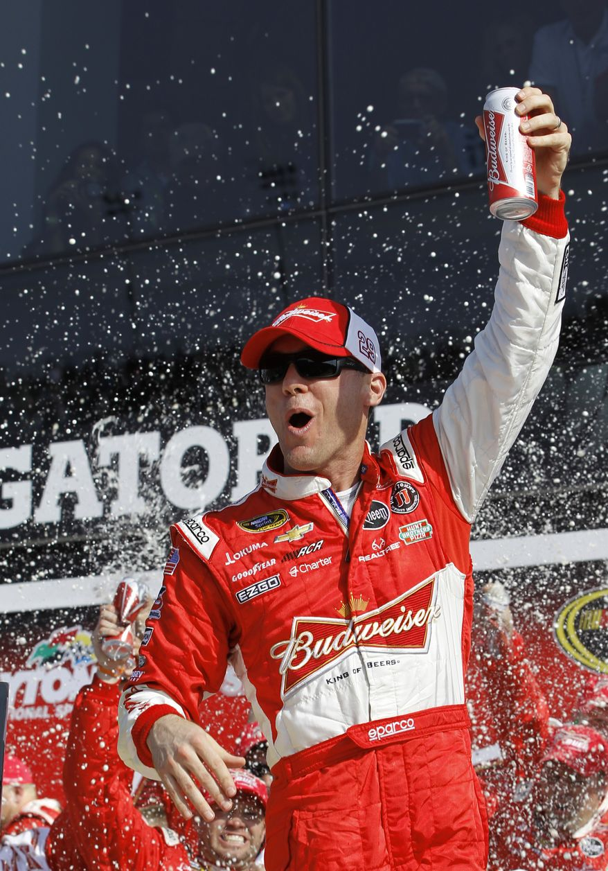 Driver Kevin Harvick celebrates in victory lane after winning the first of two 150-mile qualifying races for the NASCAR Daytona 500 auto race at Daytona International Speedway, Thursday, Feb. 21, 2013, in Daytona Beach, Fla. (AP Photo/Terry Renna)
