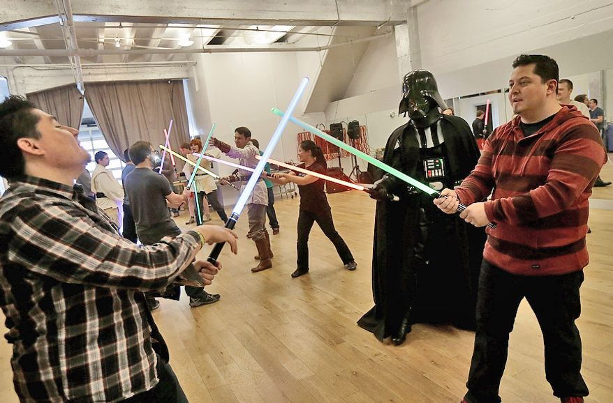 Gary Ripper, dressed as Darth Vader, gives instruction to Manny Epigmenio (left) and Adrian Gutierrez during a  Golden Gate Knights class in San Francisco on Feb. 10, 2013.  A group of San Francisco Star Wars fans who want to travel to a galaxy not that far away have created a combat choreography class for Jedis-in-training with their weapon of choice: the light saber. (Associated Press)