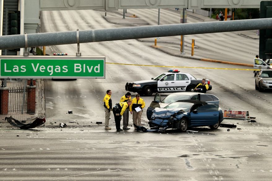 Law enforcement personal in Las Vegas investigate the scene of a multi-vehicle accident on Las Vegas Blvd. and Flamingo Road on Feb. 21, 2013. Authorities say a Range Rover opened fire on a Maserati at a stoplight, sending it crashing into a taxi that went up in flames, leaving three people dead and at least six injured. (Associated Press/Las Vegas Review-Journal)
