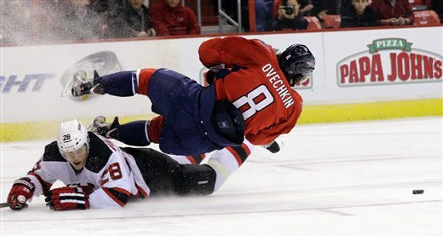 Washington Capitals left wing Alex Ovechkin (8), of Russia, loses the puck as he falls over New Jersey Devils defenseman Anton Volchenkov (28), also of Russia, in the second period of an NHL hockey game, Thursday, Feb. 21, 2013, in Washington. The Devils won 3-2. (AP Photo/Alex Brandon)