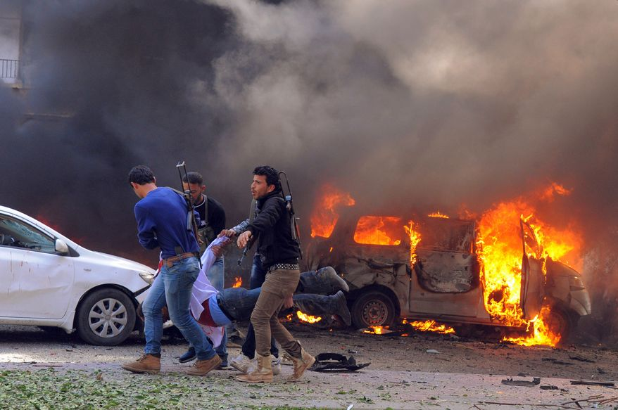 Syrian security agents carry a body following a huge explosion that shook central Damascus on Thursday, Feb. 21, 2013. A car bomb exploded near the headquarters of the ruling Baath party and the Russian Embassy, eyewitnesses and opposition activists said. (Associated Press/SANA)