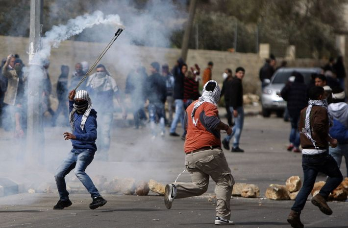 A masked Palestinian throws back a gas canister during a protest to support Palestinian prisoners, outside Ofer, an Israeli military prison near the West Bank city of Ramallah, Friday, Feb. 22, 2013. (AP Photo/Majdi Mohammed)