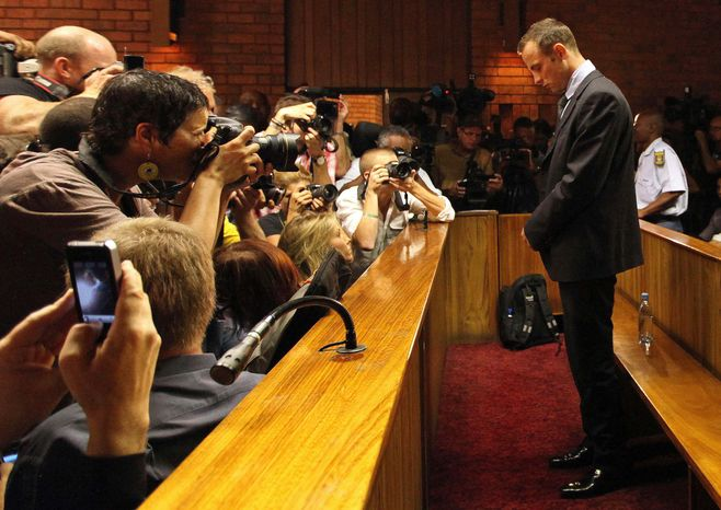 Olympic athlete Oscar Pistorius stands in the dock during his bail hearing at the magistrates court in Pretoria, South Africa, on Friday, Feb. 22, 2013. (AP Photo/Themba Hadebe)