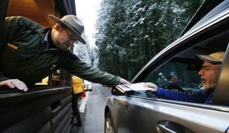 **FILE** Mount Rainier National Park Ranger Matt Chalup (left) hands park information to one of the first visitors to the park at the Nisqually entrance near Ashford, Wash., on Jan. 7, 2012. (Associated Press)