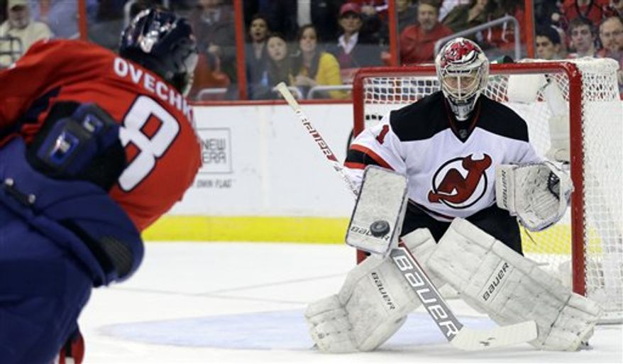 New Jersey Devils goalie Johan Hedberg (1), from Sweden, blocks a shot by Washington Capitals left wing Alex Ovechkin (8), from Russia, during the first period of an NHL hockey game Saturday, Feb. 23, 2013 in Washington. (AP Photo/Alex Brandon)