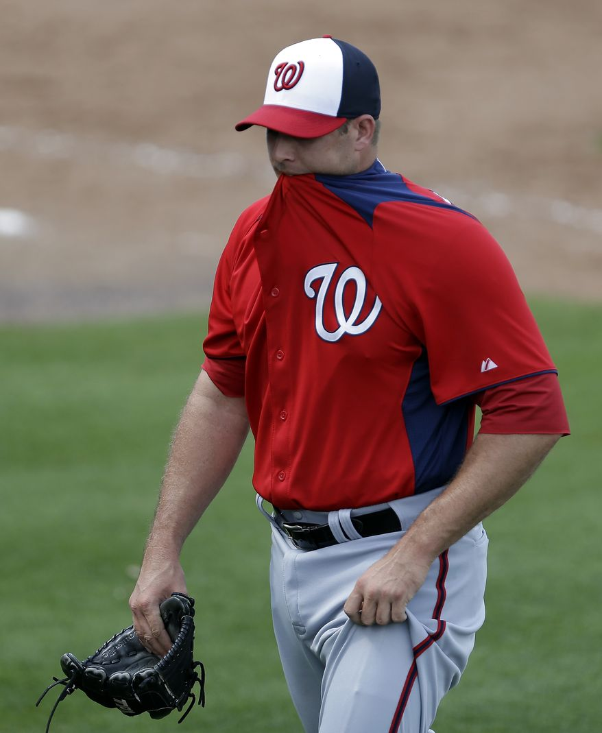 Washington Nationals pitcher Craig Stammen bites on his jersey as he walks off the field at the end of the fourth inning of an exhibition spring training baseball game against the New York Mets in Port St. Lucie, Fla., Saturday, Feb. 23, 2013, in (AP Photo/Julio Cortez)