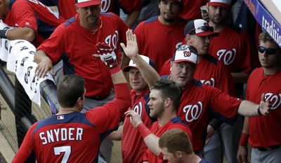 Washington Nationals catcher Chris Snyder, left, is congratulated by teammates after hitting a home run off New York Mets pitcher Shaun Marcum during the second inning of an exhibition spring training baseball game in Port St. Lucie, Fla., Saturday, Feb. 23, 2013, in (AP Photo/Julio Cortez)