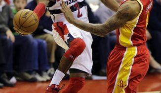 Washington Wizards guard John Wall (2) passes the ball as he is guarded by Houston Rockets forward Greg Smith (4) in the second half of an NBA basketball game, Saturday, Feb. 23, 2013, in Washington. The Wizards won 105-103. (AP Photo/Alex Brandon)