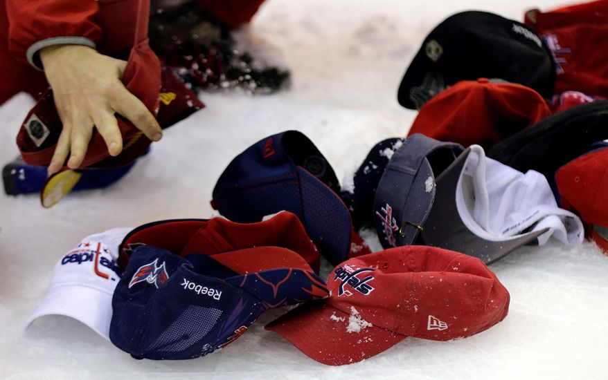 Washington Capitals hats, and others, are cleaned off the ice after left wing Alex Ovechkin's third goal of the game during the third period of an NHL hockey game against the New Jersey Devils Saturday, Feb. 23, 2013 in Washington. The Capitals won 5-1. (AP Photo/Alex Brandon)