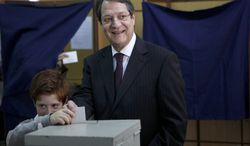Presidential candidate Nicos Anastasiades votes with his grandson Andis in the presidential election in the southern port city of Limassol, Cyprus, on Sunday, Feb. 24, 2013. (AP Photo/Petros Karadjias)