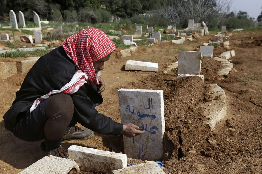 Syrian villager Abu Ibrahim, 73, writes the name of his granddaughter on her gravestone in the Jabal al-Zaweya village of Sarja, Syria, on Sunday, Feb. 24, 2013. She was killed during an airstrike by Syrian government forces. (AP Photo/Hussein Malla)