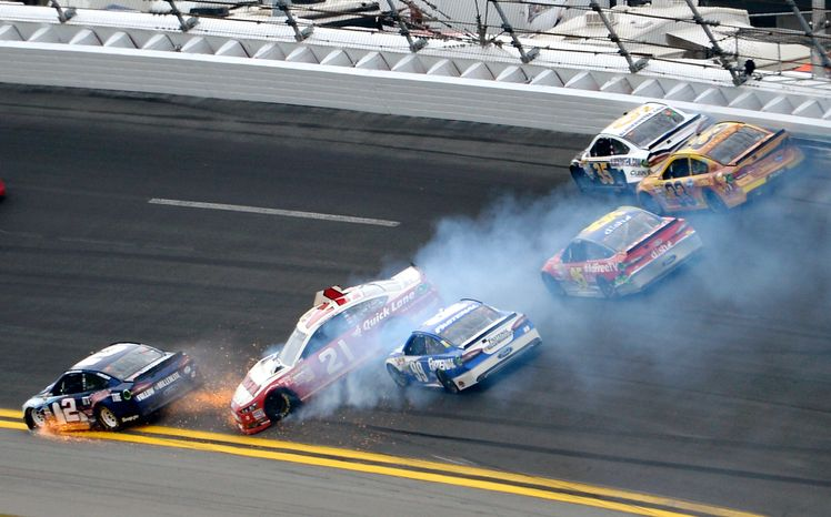 Trevor Bayne (21) spins in Turn 1 as Brad Keselowski (2) hits the apron and Carl Edwards (99), Scott Speed (95), Josh Wise (35) and Austin Dillon (33) try to avoid them during the NASCAR Daytona 500 Sprint Cup Series auto race at Daytona International Speedway in Daytona Beach, Fla., on Sunday, Feb. 24, 2013. (AP Photo/Phelan M. Ebenhack)